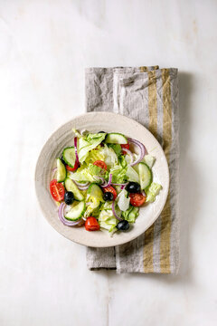 Classic vegetable salad with tomatoes, cucumber, onion, salad leaves and black olives in white ceramic plate on cloth napkin. White marble background. Flat lay, copy space