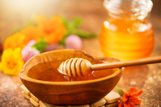 Honey dripping from honey dipper in wooden bowl.  Close-up. Healthy organic Thick honey dipping from the wooden honey spoon, closeup. Flowers and jar on the table.