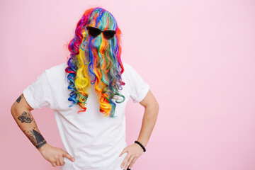Obraz A man jokingly put on a multi-colored wig and glasses on his head, posing against a pink studio background. - fototapety do salonu