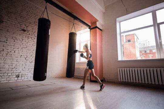 Female kickboxer hitting punching bag while dust particles flies in sunflare light background.