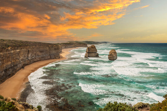 Sunrise at Gibson Steps in Port Campbell National Park, Victoria Australia with stormy oceean with waves rolling to the beach and surf against a backdrop of beautiful orange sky with clouds