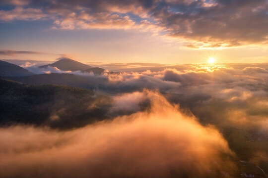 Mountains in clouds at sunrise in summer. Aerial view of mountain peak in fog. Beautiful landscape with high rocks, forest, sky. Top view from drone of mountain valley in low clouds. Foggy hills