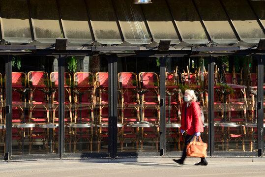 Une personne portant un masque marche devant un restaurant fermé pour cause de coronavirus à Paris, France