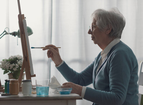 Senior woman sitting at desk and painting