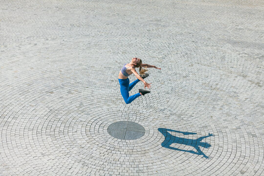 fit and muscular young woman jumping high