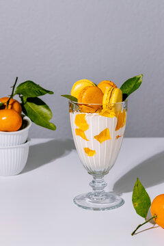 Mosaic jelly, tangerine and vanilla sour cream dessert in glass decorated with french macarons