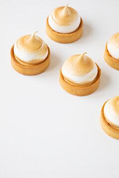 Lemon Meringue pies againsta a white background