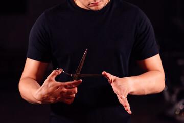 Obraz barber holds scissors in his hands - fototapety do salonu