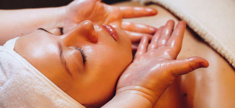 Facial massage session with special oil and cream done at the spa salon to a young woman