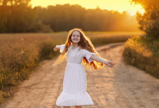 Cute girl outstretched arms enjoying sunset light.