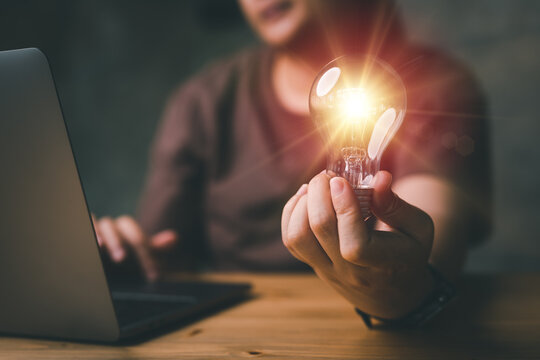 Woman hand holding light bulb and using laptop on wooden table. new idea creativity concept with innovation and inspiration