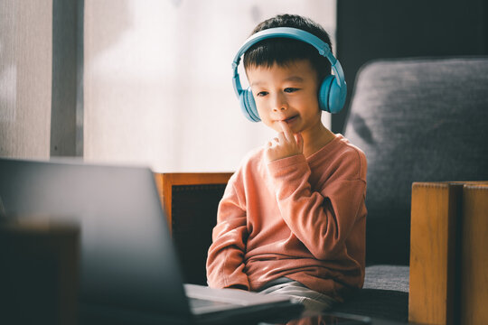 Asian boy watching and listening with laptop at home, using application online virtual class , social distancing, homeschooling, learning remotely during covid-19 coronavirus pandemic.