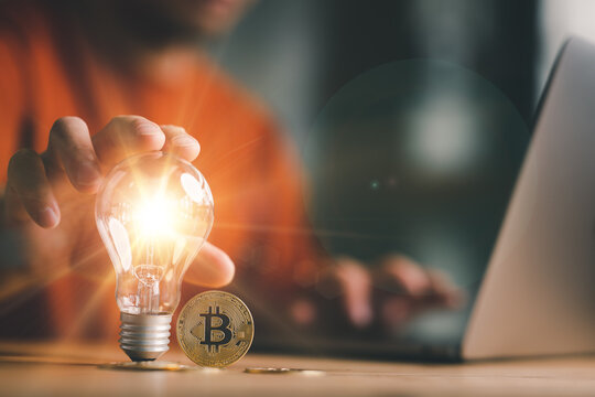 Good idea for cryptocurrency concept- digital market. man touching on lightbulb with Golden Bitcoins, Business and Finance, Savings, Investing with Digital Assets