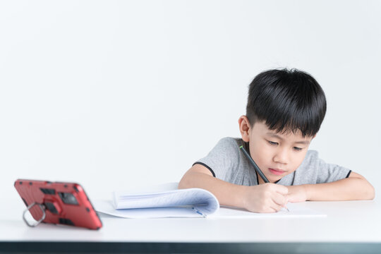 Asian boy writing while watching a mobile phone as studying online