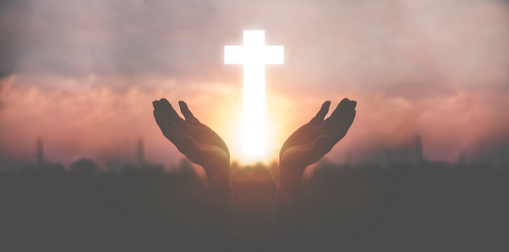Silhouette a man use hand holding wooden cross with sunset backgrounds, religion concept, international prayer day.