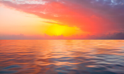 A beautiful sunset over the calm sea with red and orange clouds reflecting in the water