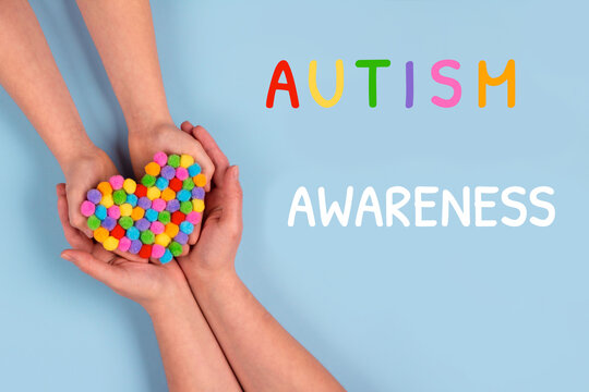 World Autism Awareness Day concept - autistic child's hands supported by mother holding multicolored heart on blue background. Autism spectrum disorder and child mental health concept. Selective focus