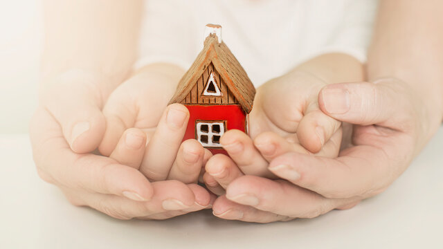 real estate and family home concept - closeup picture of child and female hands holding red paper house with family. High quality photo
