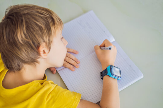 Little boy sitting at the table and looking smart watch. Smart watch for baby safety. The child makes school lessons, listening to music, calling friends