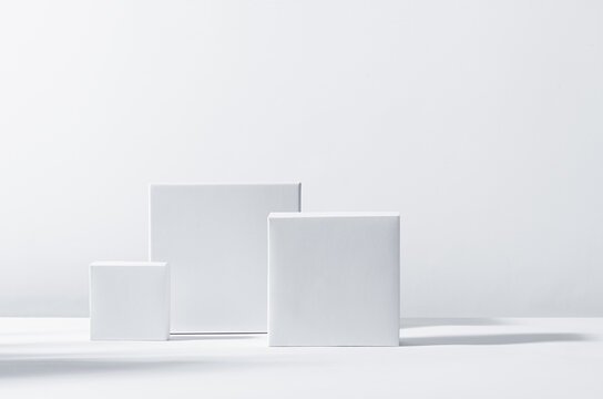 White square podiums in sunlight with shadow on white background. Trend fashion showcase for cosmetic products, goods, shoes, bags, watches.