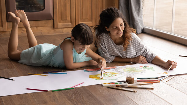 Overjoyed young Latino mother and small 8s daughter lying on floor at home have fun painting together with colors. Happy Hispanic mom or nanny and little girl child enjoy drawing. Hobby concept.