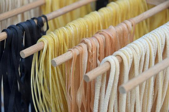 selbstgemachte frische Pasta in verschiedenen Farben hängen zum Trocknen auf einer Holzstange