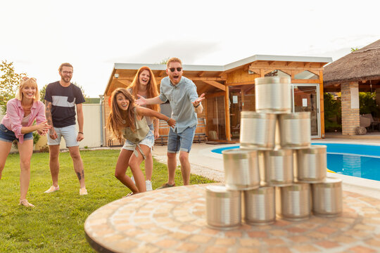 Friends knocking down pyramid of tin cans by throwing a ball at summertime party