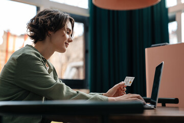 Pleased girl using credit card while working with laptop in cafe