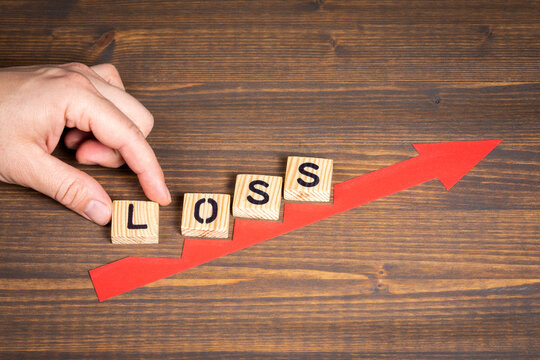 LOSS. Business and health concept. Red arrow indicates the development and growth. Steps, wooden background