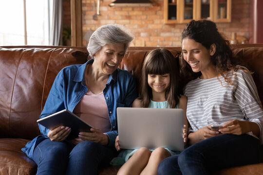Happy three generations of Latino women sit relax on couch at home using modern electronic gadgets together. Smiling little Hispanic girl with mom and grandmother rest indoors have fun with devices.
