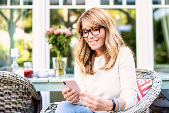 Middle aged woman using phone and text messaging while sitting on the balcony at home