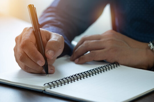 Close-up of man hand using writing pen memo on notebook paper or letter, diary on table desk office. Workplace for student, writer with copy space. business working and learning education concept.