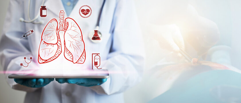 Concept of lung disease treatment. A doctor's hand holding a tablet showing a lung icon.