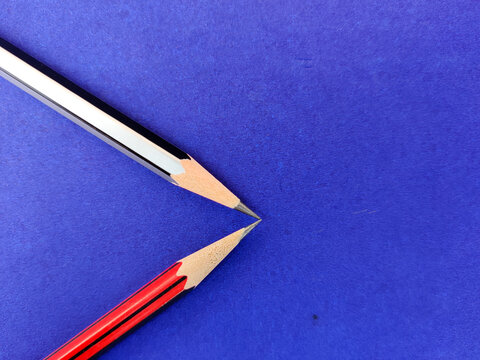 Copy space of red and black color pencil pointing each other on blue background