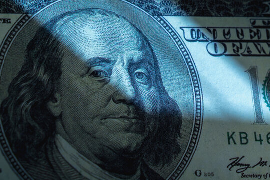 US Dllar bill in the shadow as symbol of corruption, wages in an envelope, fraud and financial manipulation