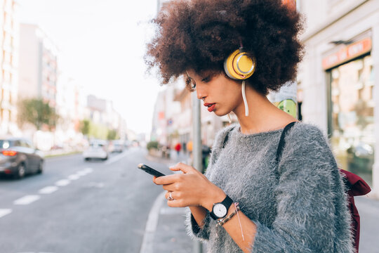 Young woman looking at phone outdoors, wearing headphones