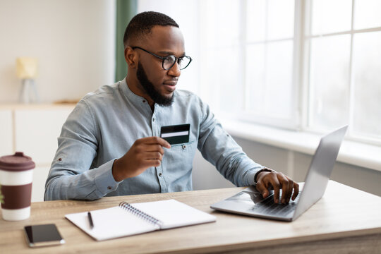African American Businessman Using Credit Card And Laptop In Office