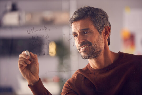 Brainstorming Businessman Or Mathematician Drawing Graph Calculation On Glass Screen In Office