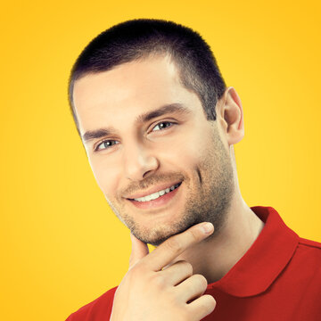 Portrait of smiling dreaming thoughtful young man in red casual smart clothing, isolated over orange yellow color background. Male caucasian model at studio. Square composition image.