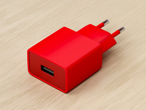 Red smartphone charger with USB port on wooden desk