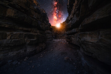 Beautiful night landscape. Red canyon at the starry night with bright bright milkyway galaxy.