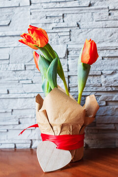 Red blooming tulips in an eco pot against the background of a gray stone wall. Spring flowers, holiday, vertical orientation