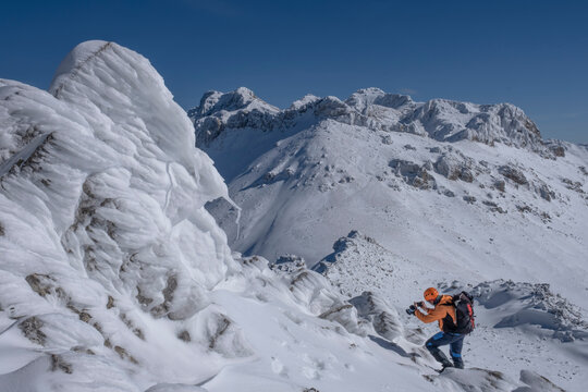 Mountaineer taking pictures in the majestic, pointed, high and scenic snowy mountains