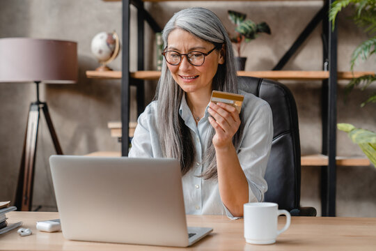 Beautiful grey-haired mature woman doing online shopping with credit card and laptop in office