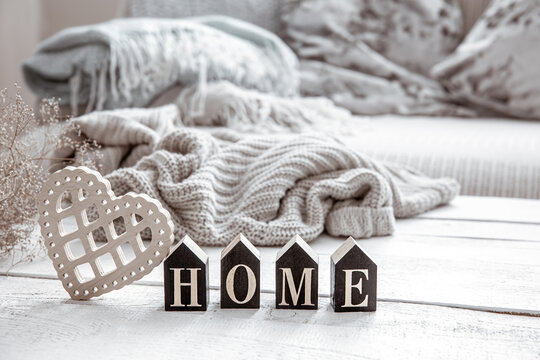 Cozy composition in Scandinavian style with decorative word home and decor details close up.
