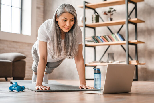 Sporty middle-aged caucasian woman standing in plank position using laptop for training at home