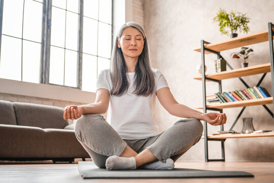 Grey-haired mature caucasian woman meditating at home