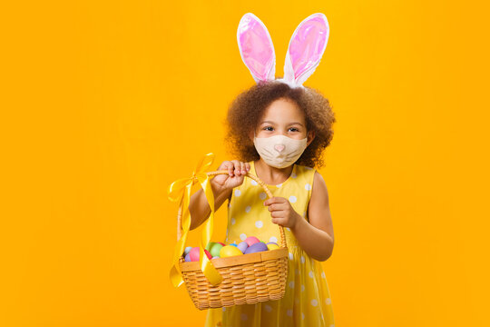 A cheerful african girl with rabbit ears on her head and a protective mask with a basket of colored eggs in her hands
