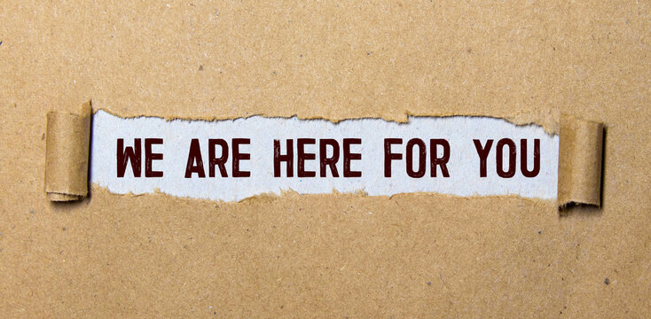 The text 'we are here for you' appearing behind torn paper. Business concept.