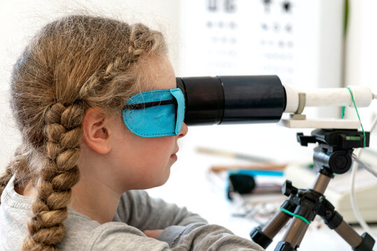 A girl is sitting in front of a device for stimulating vision.The concept of vision treatment children.Ophthalmic equipment. Orthoptic and Pleoptic Therapy.Concept of recovery and training of vision